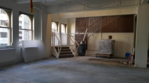 By moving the reception to the top of the stair, an open cafe? was created, which will provide a central hub for all employees. The existing panels (shown installed at the stair) will be demolished, but their structural supports will be repurposed for new transparent metal screens.