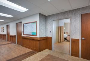 Saratoga wall protection throughout the hallways and in resident rooms and flat panel Acrovyn Doors modernize the facility.