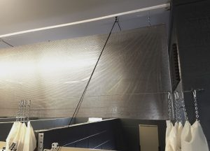 Each aluminum panel suspends from the ceiling, hanging from one edge as a banner.